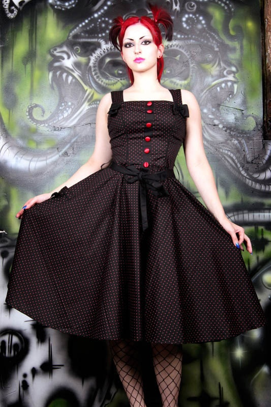 From Hell Bunny UK  Rockabilly gothic polkadot 50's dress made from slightly stretchy black cotton with red polkadots. The fitted bodice has satin covered buttons down the center front, black bows on the straps, broad straps which adjust with a button at the back and a center back zip.   The skirt flares from the waist and is great with or without a flared petticoat!