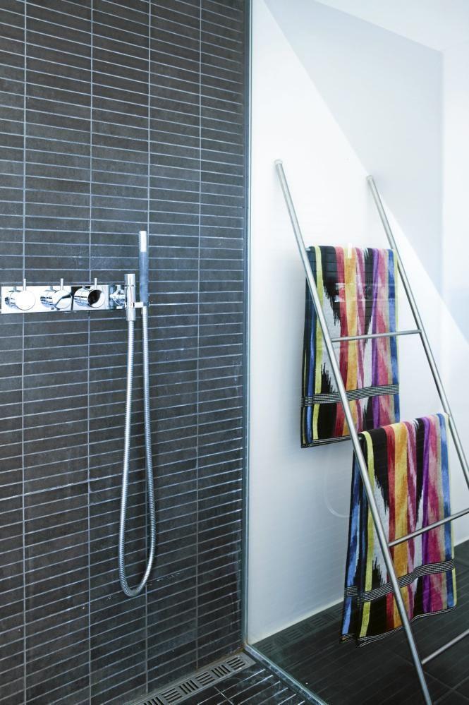 De mørke flisene på gulvet strekker seg oppover veggen i dusjen, og deler dermed opp rommet. Hånklærne henges til tørk på en vegglent stige.