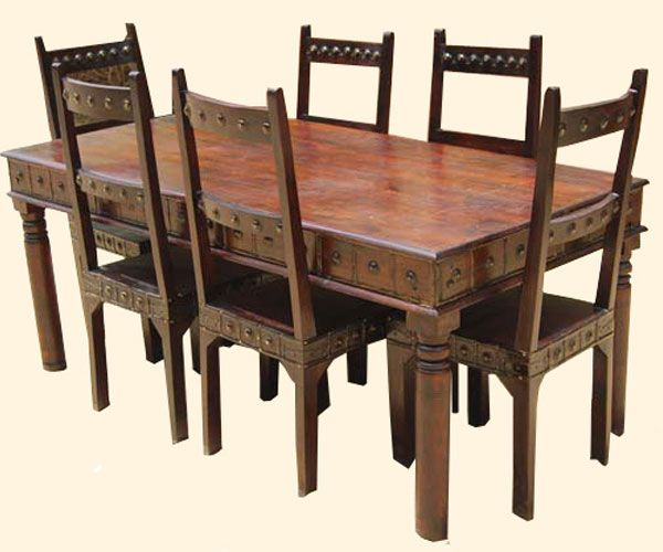 Bring a touch of medieval royalty to your home with the Camelot Mahogany 7pc Dining Table and Chair Set. This handmade furniture set features school back chairs with iron accents on the table and chairs reminiscent of Arthur of England.