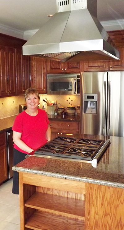 one of our customers showing off her new stainless steel island range hood from proline range