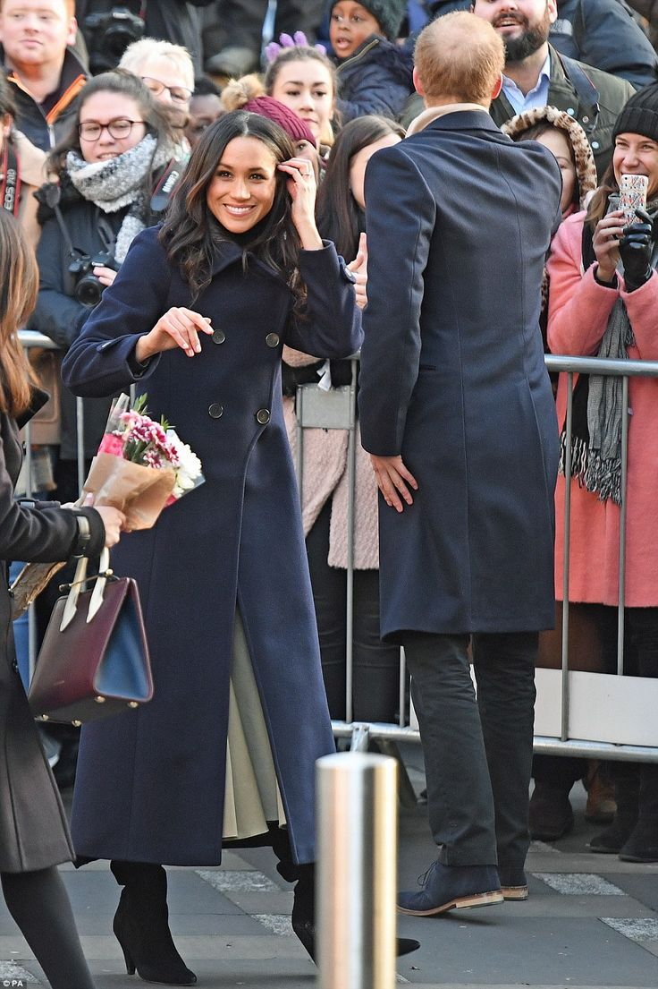 Ms Markle was wrapped up against the cold in a long dark blue coat by Mackage, and boots...