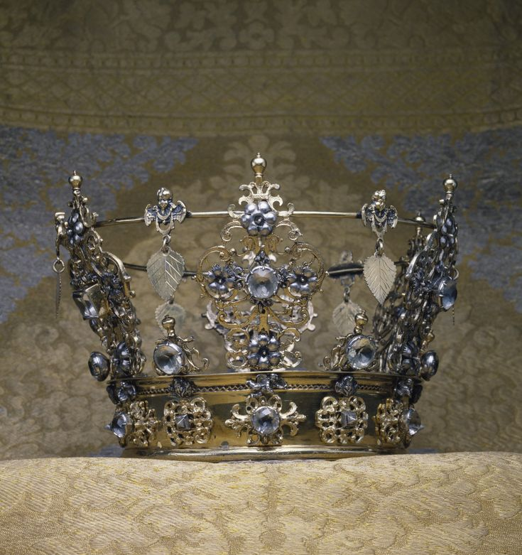 Swedish Wedding Crown, early 18th century, silver gilt with paste jewels, 5 7/8 in. (14.9 cm), Although crowns are customarily associated with royalty, wedding crowns in Scandinavia were worn by brides of all social strata. They were owned by the bride's parish and loaned for the occasaion. Wedding crowns were richly decorated with emblems of conjugal love: this example includes carnations,