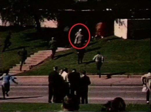 """1963-11-22: The """"Babushka Woman"""" climbing the steps in Dealey Plaza leading to the grassy knoll."""