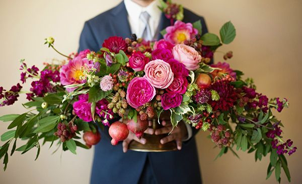 A beautifully bright horizontal arrangement overflowing with roses, dahlias, pomegranates, berries, bougainvillea, and greenery | Photo by Rapp Photography | Floral design by City Blossoms