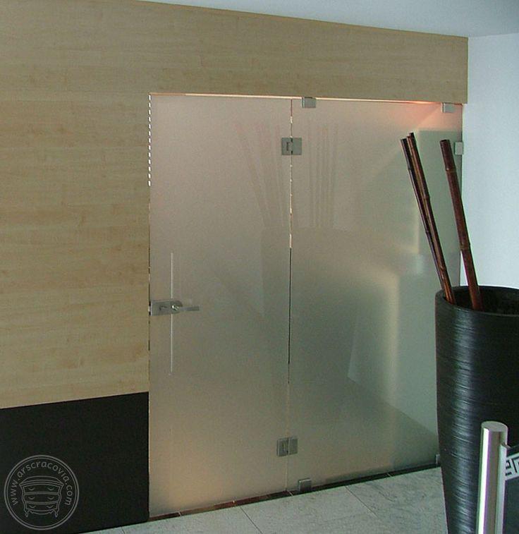 Ścianka z laminowanego mdf-u i szkła, połączona z ladą i szafkami, wydzielająca hotelową recepcję.