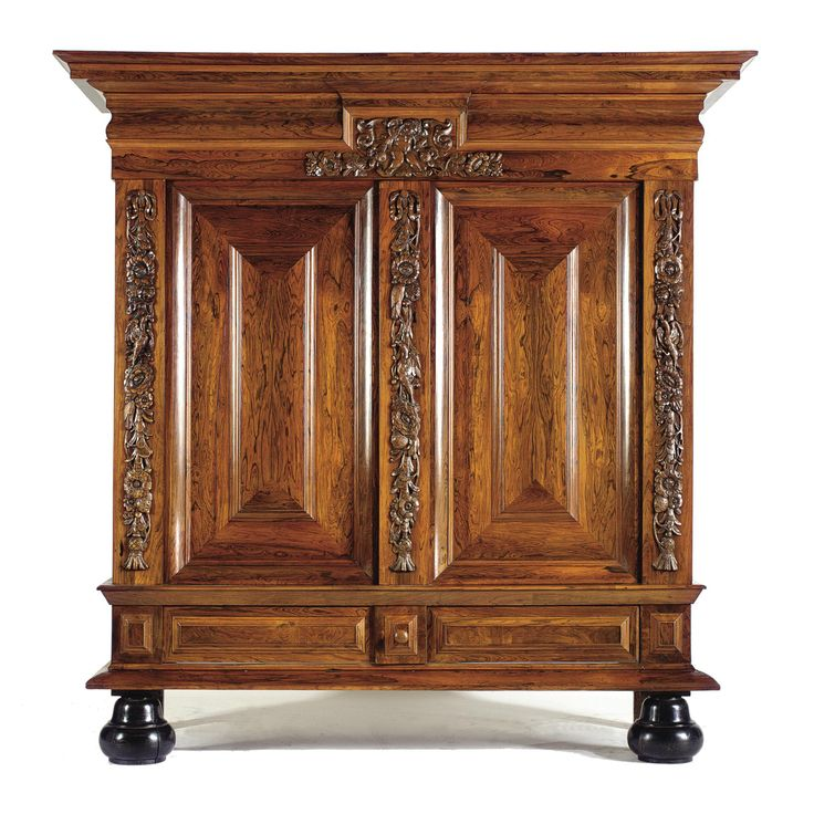 A DUTCH ROSEWOOD TWO-DOOR CUPBOARD BAROQUE, CIRCA 1700 with two panelled doors beneath putto carved cresting, flanked and divided by floral and bird carved ornaments, with long drawer, on bell feet height 215cm., width 214cm., depth 70cm.