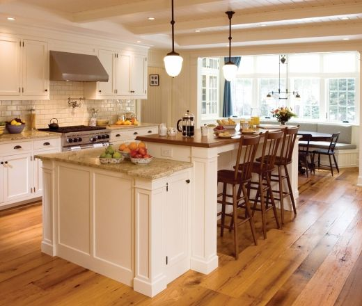 Traditional white kitchen blends well with natural wood floor, accents.