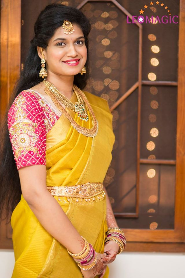 South Indian bride. Gold Indian bridal jewelry.Temple jewelry. Jhumkis.Yellow silk kanchipuram sari with contrast pink embroidered blouse. Half updo with maang tikka.Tamil bride. Telugu bride. Kannada bride. Hindu bride. Malayalee bride.Kerala bride.South Indian wedding.