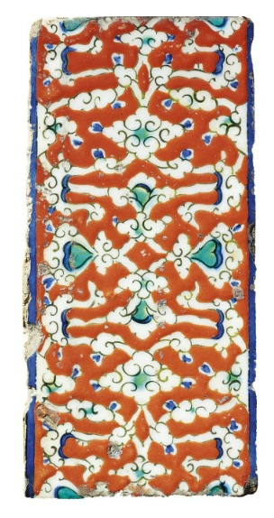 AN IZNIK BORDER TILE   OTTOMAN TURKEY, CIRCA 1570   Of rectangular form, the bole-red ground with a complex design of interlaced cloudband motifs outlined in black and highlighted in cobalt-blue and green, plain thin cobalt border, chips to edges and minor area of flaked glaze  4¾ x 10in. (12 x 25.2cm.)