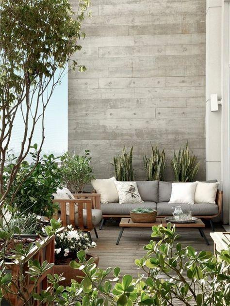 decoracion jardin, terraza con suelo de tarima, mesa y sofá con cojines beige y gris, plantas verdes
