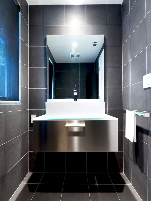 For this small bathroom, designer Kriste Michelini created a luxury hotel feeling by using the same tile on the floor and walls.