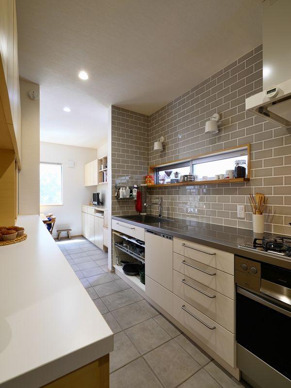 グレータイルの壁と収納たっぷりのキッチン リビング キッチン