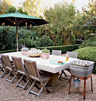 gravel patio. teak folding chairs. concrete table? old wash tub as ice bucket/cooler. boxwood hedges