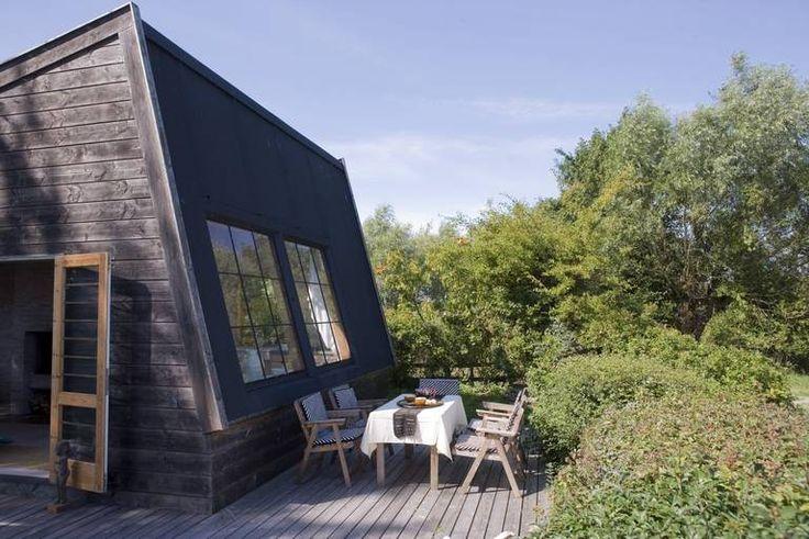 UTEROM: Plattingen i lerk skaper et klart definert uterom som kontrast til den frie naturen rundt hytta. Utvendig kledning er Douglasgran. Hytta er tegnet og bygget av en båtbygger.