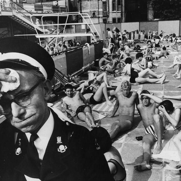 Un infermiere dell'ambulanza, in servizio alla piscina Holborn Oasis di Londra, si asciuga il sudore mentre le altre persone prendono il sole, probabilmente nel 1964