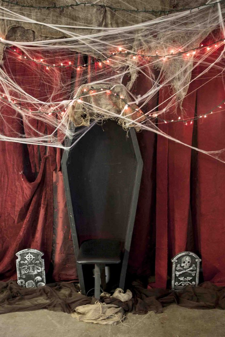 halloween party photo op spot in the lounge using an old open coffin some cobwebs red string lights and dollar store tomb stones surrounded by brown - Vampire Halloween Decorations
