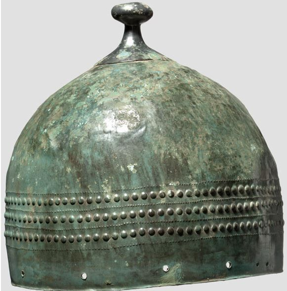 Central European helmet, Bronze Age, circa 1000 B.C. Bronze with beautiful dark to bright green patina. One-piece skull, some parts with small cracks and replacements. Six-fold riveted crest plate with swamped crest pommel. Continuous frieze made from regularly arranged studs and points. The lower rim is an addition in brass with holes for the lining as well as two pairs of holes to attach the cheek-pieces, 23 cm high. Private collection, from Hermann Historica auction