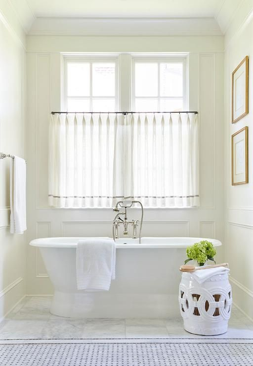 Chic bathroom nook is clad in decorative wall moldings filled with a roll top tub and a vintage hand held tub filler as well as a white rope stool placed under windows dressed in white sheer cafe curtains accented with gray trim.
