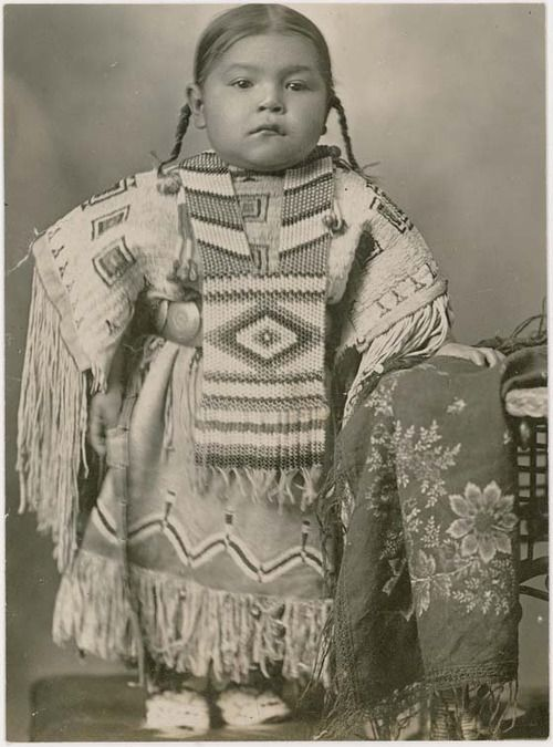 Cheyenne girl wearing an elaborate beaded dress and breastplate, 1915. Oklahoma.