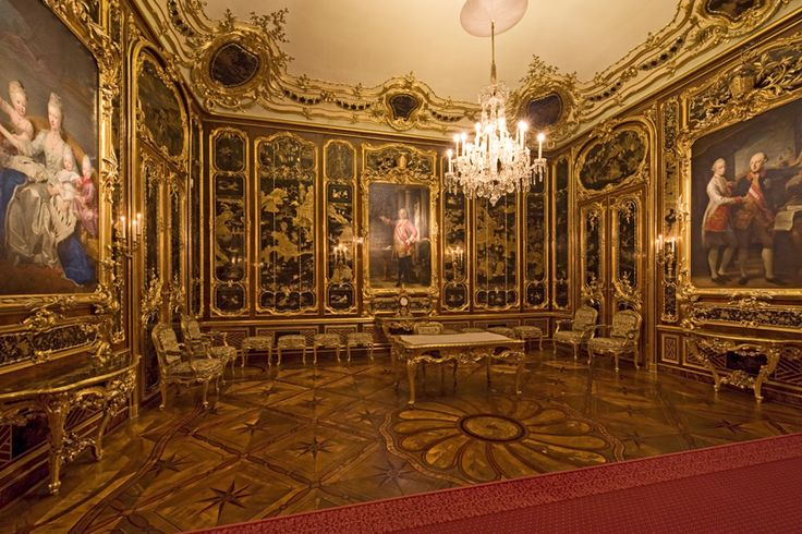 Hapsburg family portraits framed in gold and black lacquer inlaid onto walnut paneling at Schoenbrunn Palace
