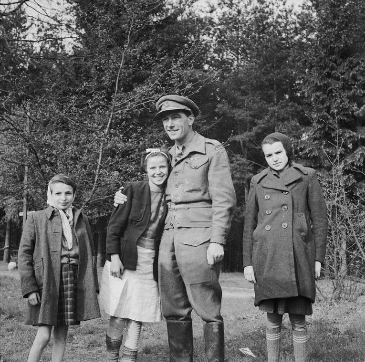 THE LIBERATION OF BERGEN-BELSEN CONCENTRATION CAMP, APRIL 1945. Major E M Griffen RAMC, Commanding Officer of No 7 Mobile Bacteriological Laboratory, with children in Camp No 2 at Hohne Barracks. Over twenty six days, Major Griffen's unit cleaned and disinfected 11,000 camp inmates.