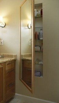 Built-in bathroom storage and a full length mirror... what a great idea... who doesn't need more storage? Just cut in between the frame boards, frame it, paint it, and hang a mirror on heavy duty hinges. And if you don't want the mirror put a cabinet door up :).