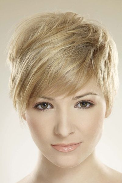 Delicate pixie cut with soft blonde colouring This is a really cute look as this woman's short layered hair has been brushed over at the front of the face. Long bangs are styled across on the forehead leaving this a chic style. The hair is cut short. Tech