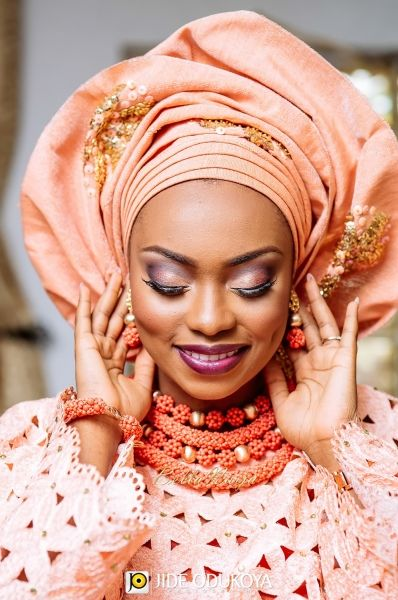 beautiful Nigerian bride in light coral peach pink color dress and gele and gold and coral bead necklace. Atinuke & Femi Odukoya | Yoruba Lagos Nigerian Wedding | Jide Odukoya Photography | BellaNaija 006