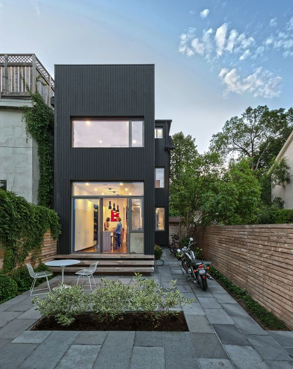 """The team carried the concept of contrast through the exterior, juxtaposing the home's 125-year-old red brick façade with vertical, black-stained cedar cladding at the back. """"We wanted to celebrate the old alongside the new,"""" Dubbeldam says. Since the house is so well insulated, the extra heat that dark exteriors typically draw doesn't penetrate beyond the boards' surface. Courtesy of Bob Gundu."""