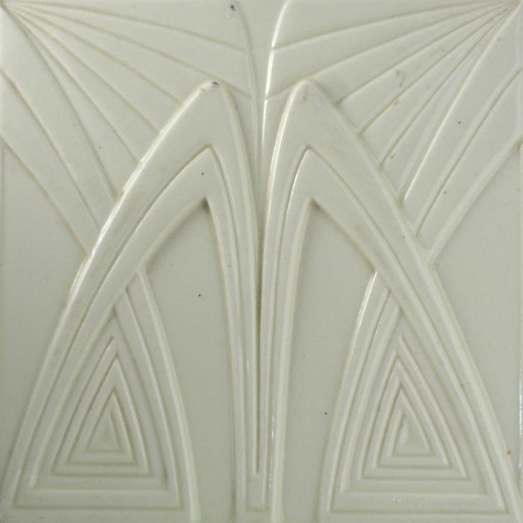 A high relief moulded cream ground tile with a bold modernist angular design of overlapping ribbed forms. Condition: one or...
