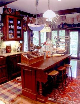 A collection of antique stools line up at this antique kitchen island, formerly a piano, where once a player and bench would have sat. Colorful rugs, glass-front cabinetry, hardwood flooring, baskets and open shelving make the kitchen feel like an old-time general store.