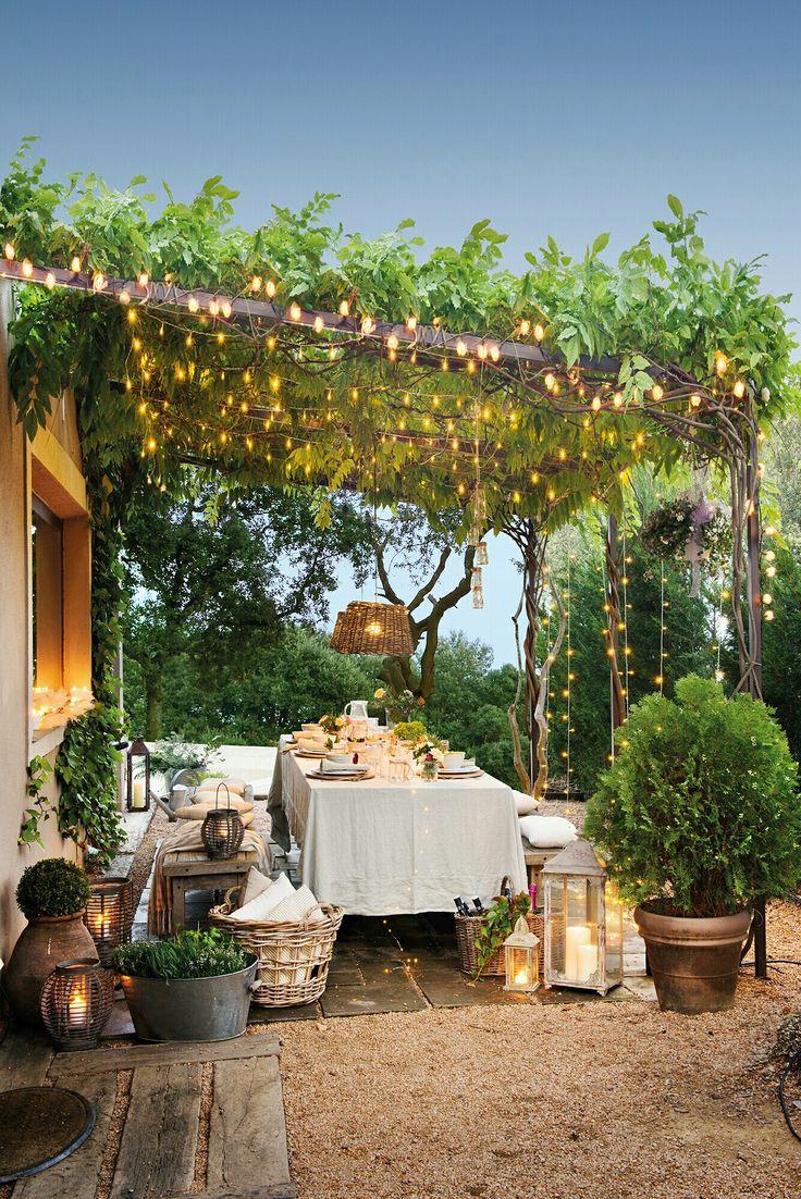 Essbereich im Freien unter einer mit Weinreben bewachsenen Pergola mit Holztisch und Bänken sowie vielen Lichterketten   – zhanghua