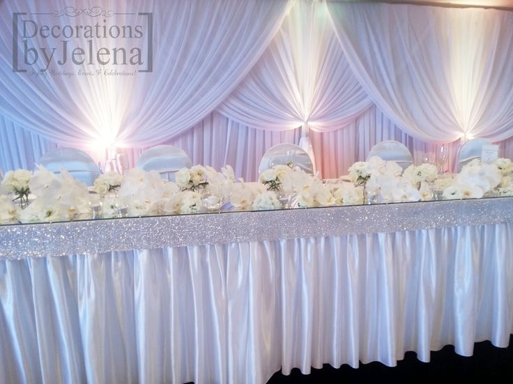 Luxe seaside all white beach wedding reception main table styling with fresh flowers candles backdrop skirting and crystal details - Decorations by Jelena