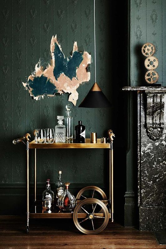 Dark green room with a beautiful wallpaper and a golden bar cart. The bar cart makes this room look very classy and expensive.