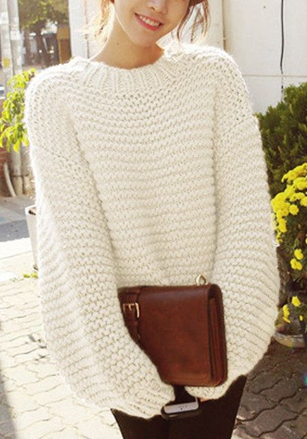 Front shot of model in a beige knit bishop-sleeve sweater and brown bag