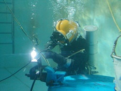 Student diver practicing underwater welding in the main training tank at the International Diving Institute (IDI).