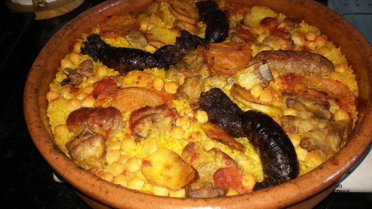 """ARROZ AL HORNO """"A MI MANERA"""" 2 tazas de arroz, 4 tazas de caldo de cocido, 1 bote de garbanzos, 100gr de tomate triturado, morcillas de cebolla (1 por comensal), blanquets (1/2 por comensal), 400gr de costillas de cerdo, 1 tomate en rosajas, 1 patata en rodajas, 1 cabeza de ajos, sal, AOVE y colorante o azafrán.   Salar las costillas y sofreir junto a las morcillas, los blaquets y la patata en rodajas. Reservar. Sofreir el tomate triturado, los ajos, los garbanzos y el arroz,...."""