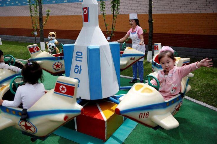 Дети катаются на карусели во время организованного правительством визита иностранных репортёров на текстильную фабрику Ким Чен Сук в Пхеньяне. В суровой милитаристской стране даже карусель должна напоминать о героических военно-воздушных силах.