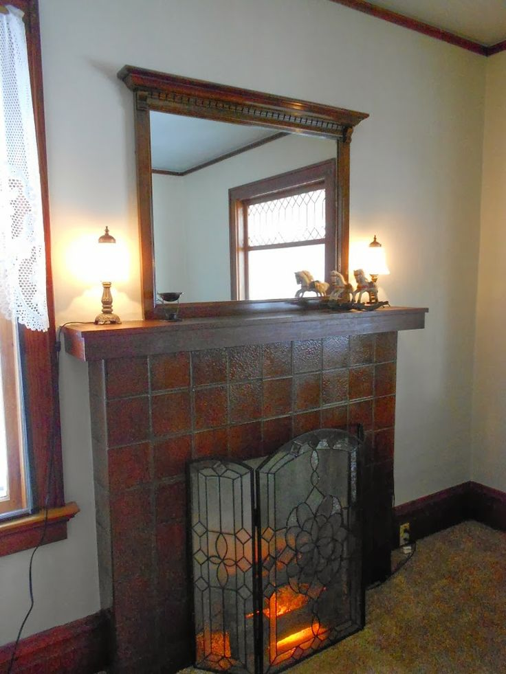 Put the mirror up and it looks great!   added a leaded glass fireplace screen.... covering for now faux electric log fireplace.  This spring we are carefully cutting out the center area of cement and installing a gas log direct vent fireplace unit.  We will retain the original mantel and tile surround....  and set the screen back in place when done. The leaded glass screen is the FIRST thing we bought when we put the offer in on the house, and started collecting things to go in the house.