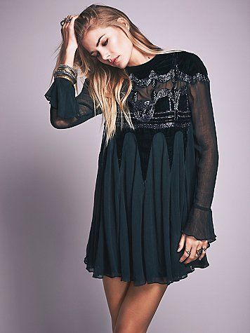 Fall In Love Tonight Dress | Equal parts ethereal and whimsical, this babydoll style dress features beautiful embroidered beading and velvet paneling. Sheer bell sleeves and button back closure for an easy fit. Full slip included.