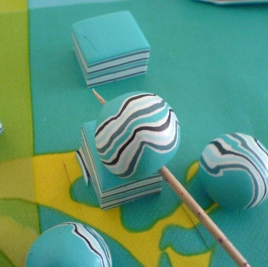 Roll layers of colours, lay them on top of one another, cut into squares & gently roll into round beads :)
