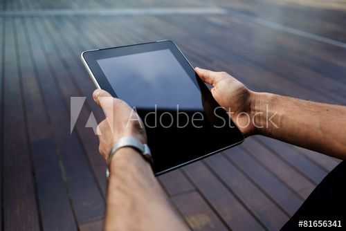 Male student hands with touchpad against wooden background