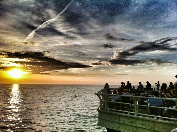 Cromer pier and a crowed gathered to watch the sunset
