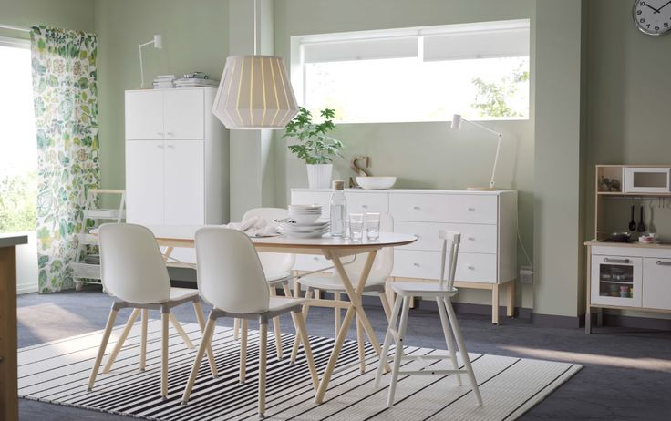 A large dining room with a dining table in white and solid birch combined with four chairs and a junior chair. Completed with a high cabinet and two chest of 3 drawers, also in white and solid birch.