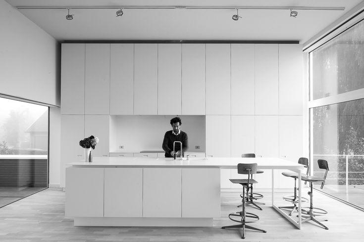 Strakke witte keuken met hoge kasten en eiland - foto van Cafeine / architect D' Hooge-Meganck