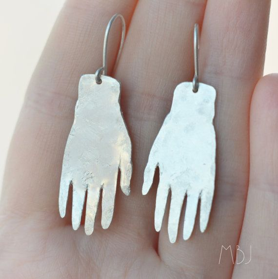 This is a sterling silver (hallmarked) earring made in my studio.  This pair was inspired by the earrings of the painter Frida Kahlo, who was best known for her brave self portraits. The white hand earrings were one of her favourite earrings to wear and can be seen on some of her work.  I made these earrings out of solid sterling silver sheet and earwires. The sterling has some texture for a bit of fun and a lot of shine. I also have a darker version of this earring (with patina and shine)…