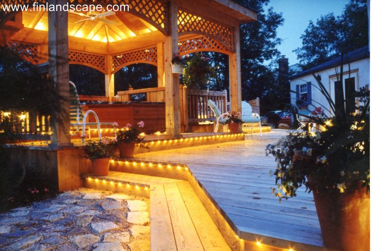 Contemporary style cedar deck with an open gazebo including a spa under. Gazebo and all steps illuminated with landscape lighting for safety and night time entertaining.