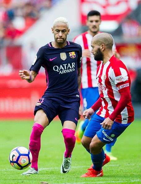 Neymar of FC Barcelona duels for the ball with Alberto Lora of Real Sporting de Gijon during the La Liga match between Real Sporting de Gijon and FC...