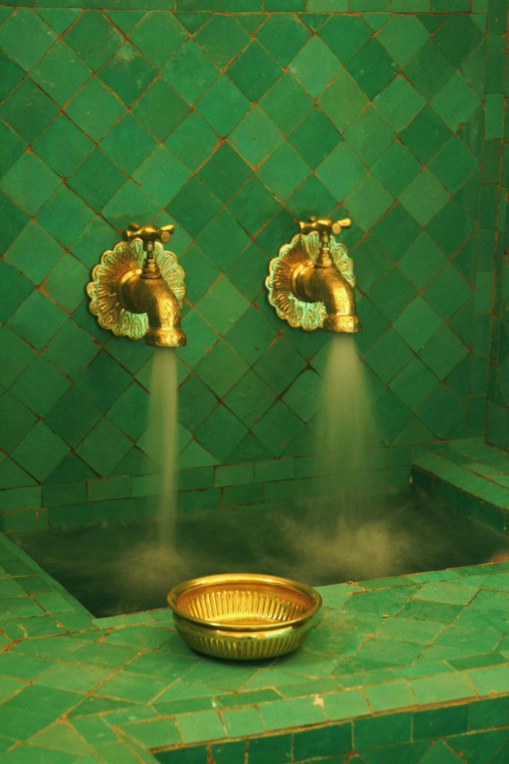 a turkish bath with green tiles and gold-colored brass taps. the color combo is quite pre-raphaelite.