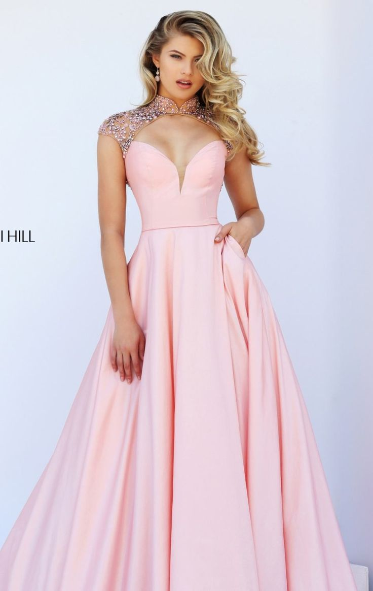 Elegance is yours in Sherri Hill 50004. This dress features a high neckline of sheer fabric heavily decorated with glistening beads draping over the cap sleeves. The diamond opening at the back works perfectly with the exciting cutout in front showcase a daring peek of your gorgeous allure. The full ball skirt make this dress even more glamorous.